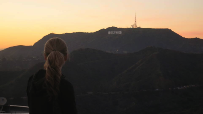 Woman looking at the Hollywood sign at sunset